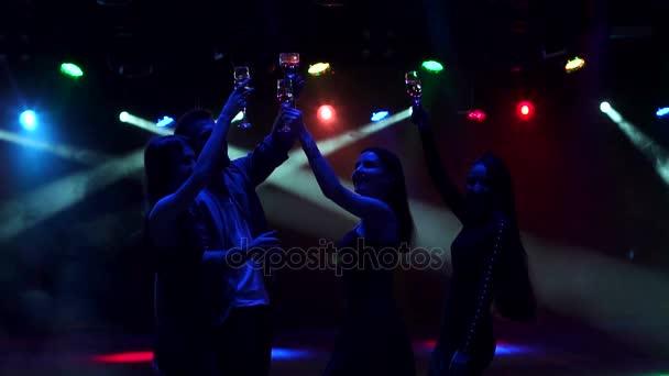 Sziluettjét táncoló emberek pezsgővel.