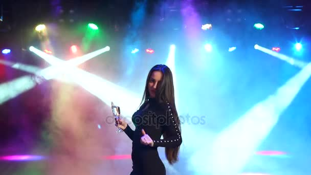 Portrait of a girl with champagne dancing at party