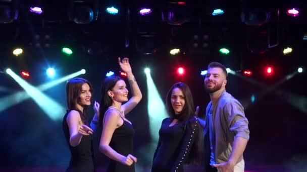 vier Freunde tanzen im Nachtclub im Dunkeln