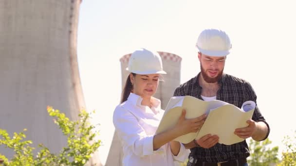 Ingenieurinnen und Ingenieure untersuchen Bauplan.