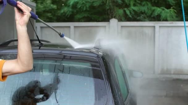 Mladý muž mytí auta na samoobslužné mytí aut