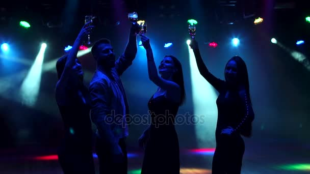 Friends dancing with champagne in hand at party.