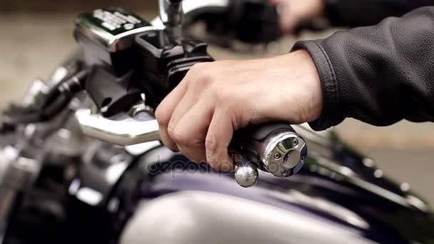 Člověk vymáčkne spojku na řidítka motocyklu.
