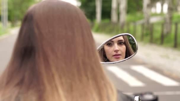 Mädchen bemalt ihre Lippen beim Blick in Motorradspiegel.