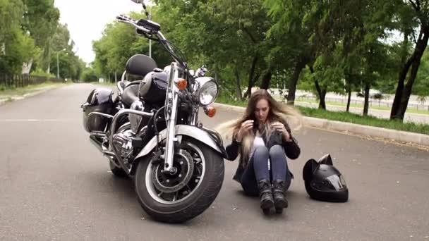 Kostým motorkářka sedí na zemi ležel vedle motocyklu.