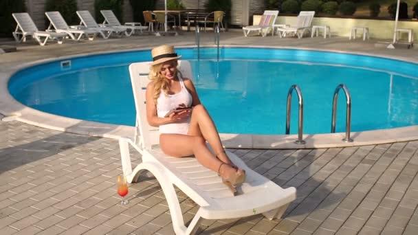 Lány pihentető medencében úszás után egy tabletta.