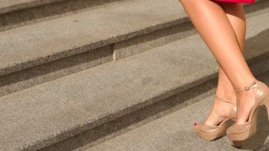 Close-up of a girl in high heels climbs the stairs