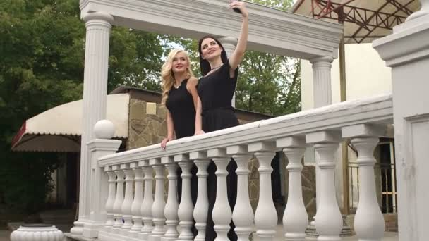 Two girls in black evening dresses take a selfie.