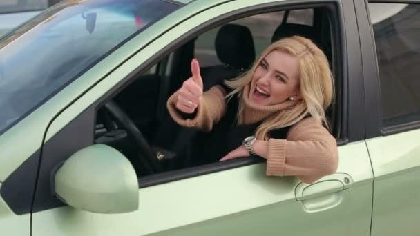 Happy usmívající se dívka v autě ukazuje palec.