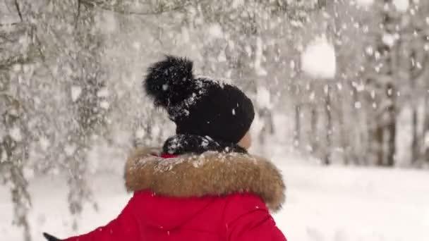 Šťastná dívka spinning pod těžký sníh v parku