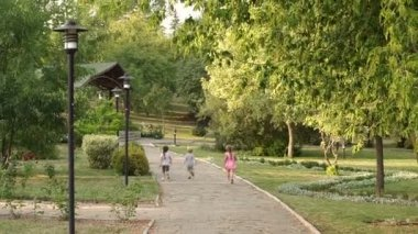 Three children running along the alley in the Park