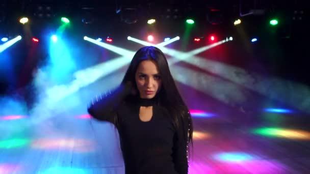 Szexi lány táncol spotlámpák fényében.