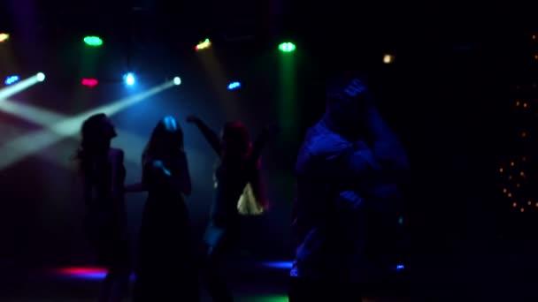 Csoport fiatal táncos a sötétben. Sziluettjét
