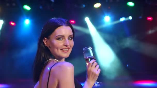 Lány pezsgővel sötétben közelében koncert világítás