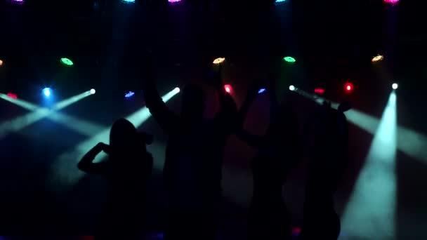 Silhouette junger Menschen, die in einem Nachtclub tanzen.