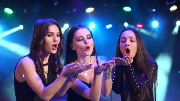 Tři dívky vyfukování barevné konfety na večírku