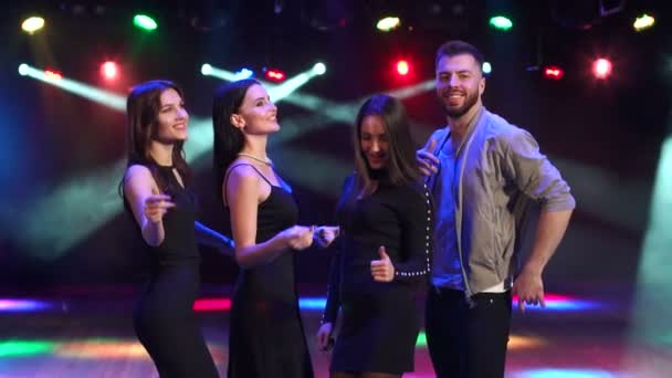 Four friends dancing in the night club in the dark