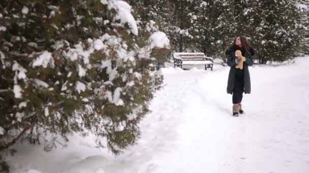 Happy pregnant woman walking in park in winter.
