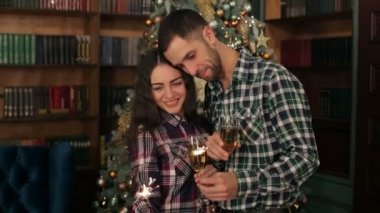 Couple with champagne and Bengali lights by tree.