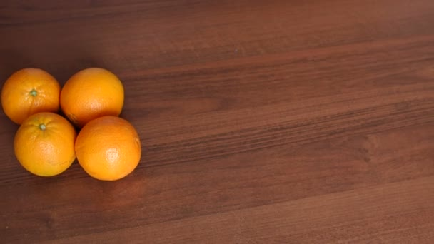 Čtyři zralé šťavnaté pomeranče na dřevěné pozadí