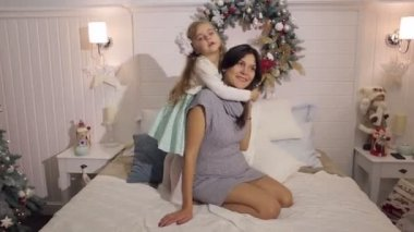 The daughter hugs her pregnant mother on the bed.