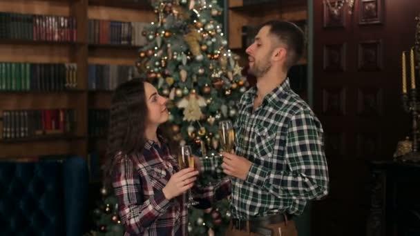 Porträt eines Paares mit Champagner an einem Baum.