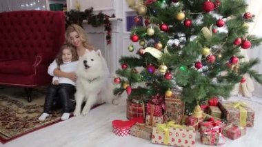 Happy family with a dog near a Christmas tree.