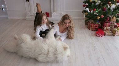 Mother and little girl stroking a big fluffy dog.