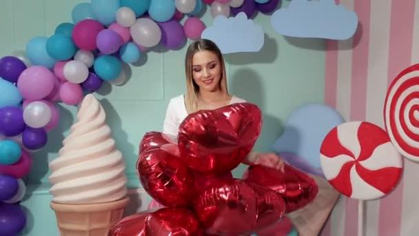 Porträt eines Mädchens mit Luftballons in Herzform.