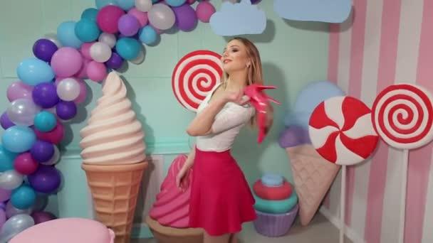 Barbie dívka s boty v ruce poblíž obrovské sladkosti