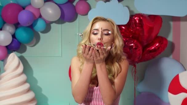 Dívka foukání na konfety party candy pomalu