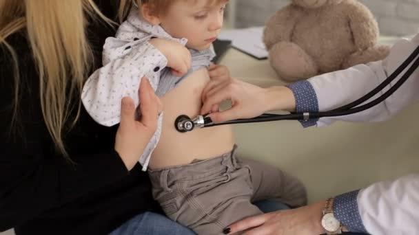 Kinderarzt untersucht kleinen Jungen mit Stethoskop