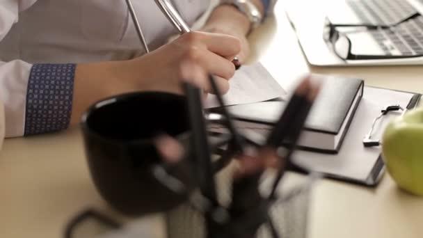 Arzt ein Rezept auf seinem Schreibtisch zu schreiben