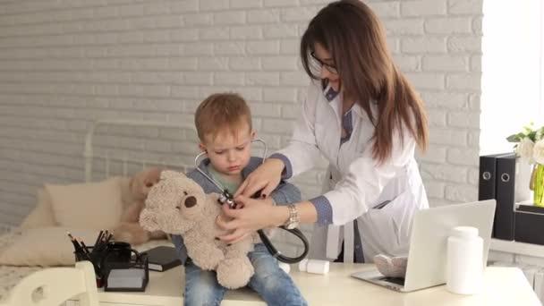 Arzt und jungen Patienten untersuchen Teddybär