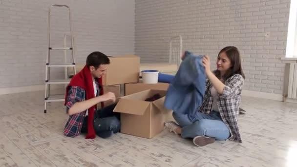Veselý a šťastný pár rozbalení krabice na podlaze