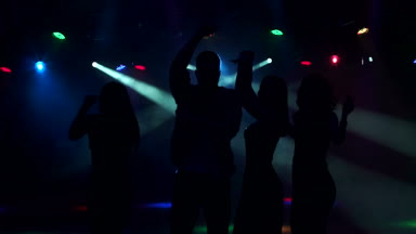 Four friends dancing at the party in the dark.