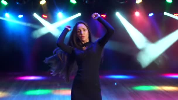 ein sexy Mädchen mit langen Haaren tanzt in einem Nachtclub.
