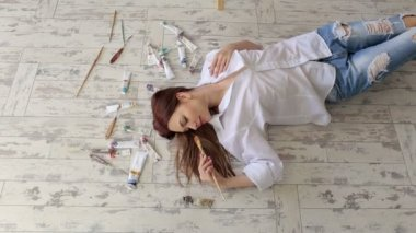 Portrait of a girl artist with paints on a floor.