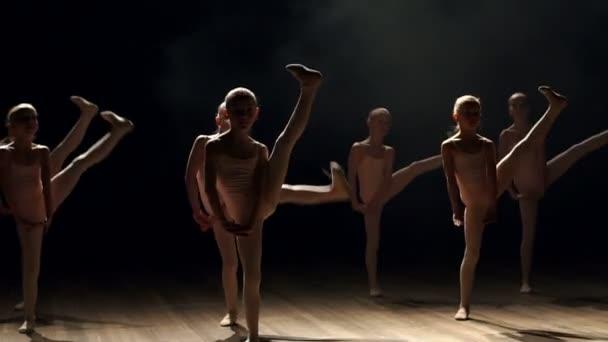 Malé děti tančí balet na jevišti. Balet