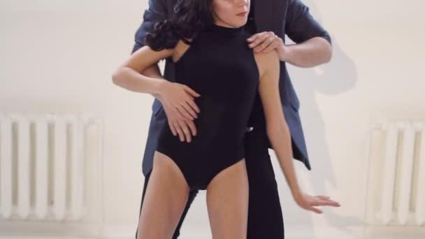schönes Paar tanzt Bachata im weißen Raum.