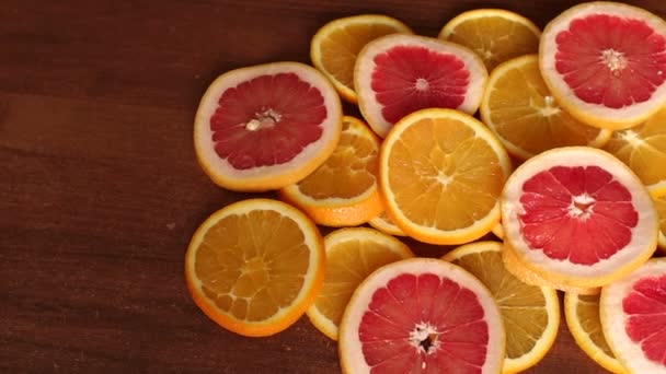 Sliced oranges and grapefruit on wooden table. CU