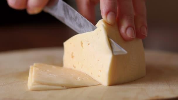 Žena kusy sýra na řezací desky, detail.
