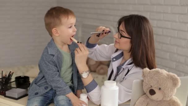 Kinderarzt untersucht Kehle eines kranken Jungen.