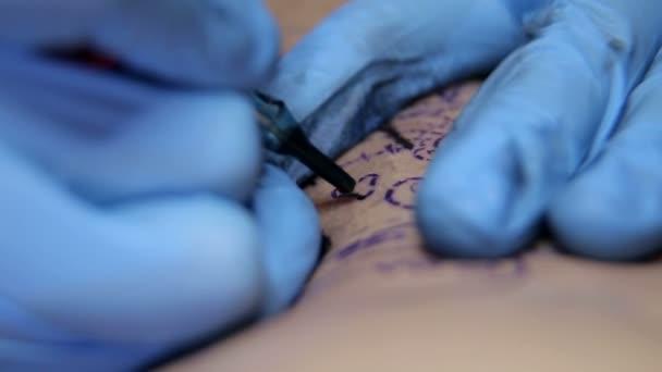 Professional artist making tattoo in salon.