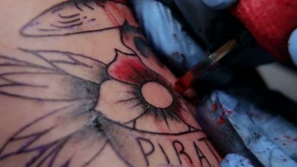 Professional tattooist doing tattooing in studio.
