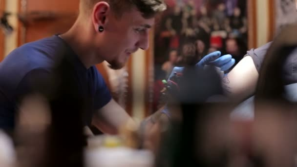 Master doing tattooing in tattoo studio.