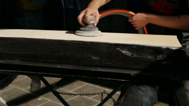 Mechanik brousí část auta pro malování. Opravář broušení a leštění karoserie