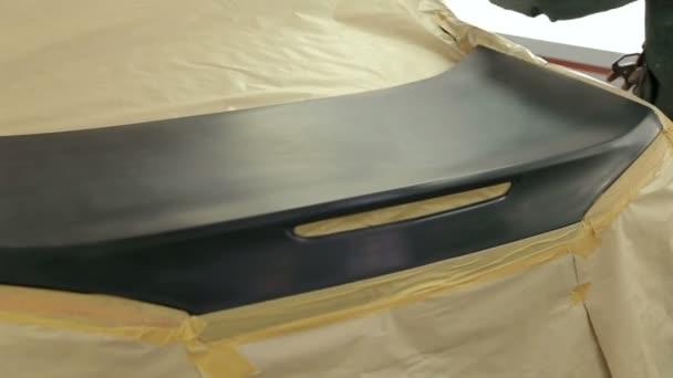 Detailní záběr mechanických barev na nárazník a kufr auta stříkající černou barvu
