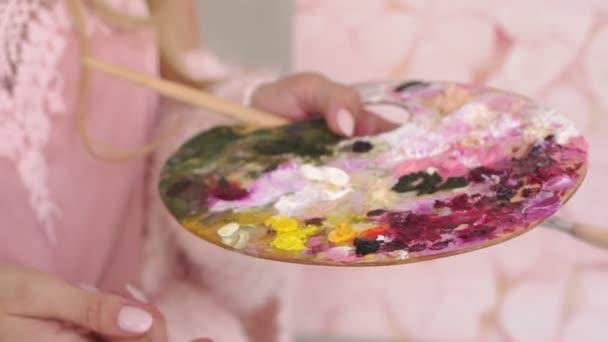 Nahaufnahme des Mädchens mit einer großen Palette von Farben und Pinseln zum Zeichnen.