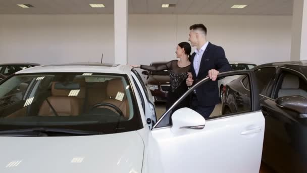 A young couple in love buys a car in the showroom. Buying or renting a car.
